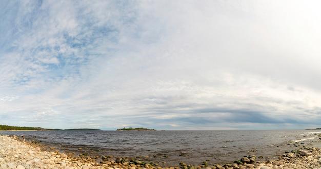 O céu acima da praia de seixos no lago.