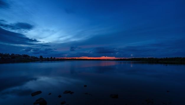 O céu ao pôr do sol refletido na água do lago.