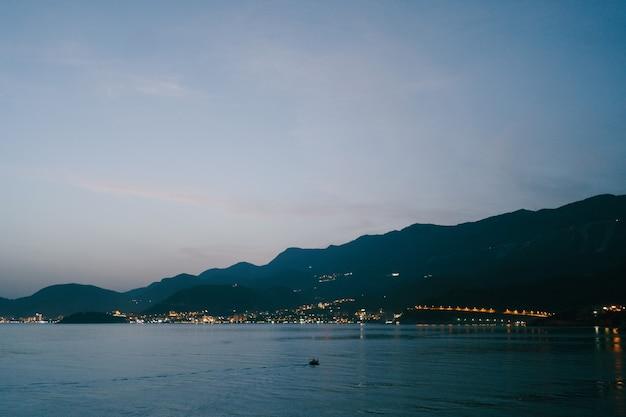 O céu após o pôr do sol sobre budva em montenegro as luzes da cidade à noite