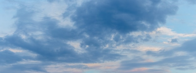 O céu azul coberto de nuvens escuras ao anoitecer