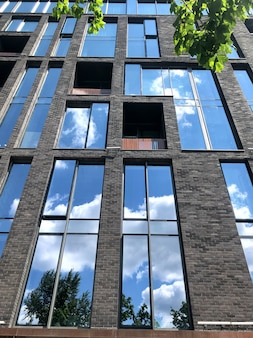 O céu azul é refletido nos painéis das janelas de um edifício moderno