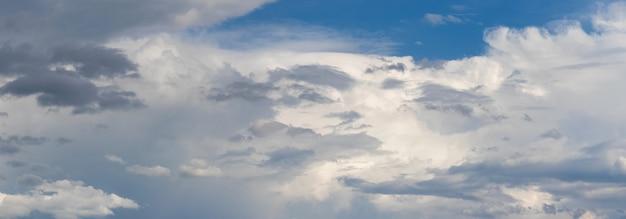 O céu azul está coberto por várias nuvens claras e escuras, o céu depois da chuva