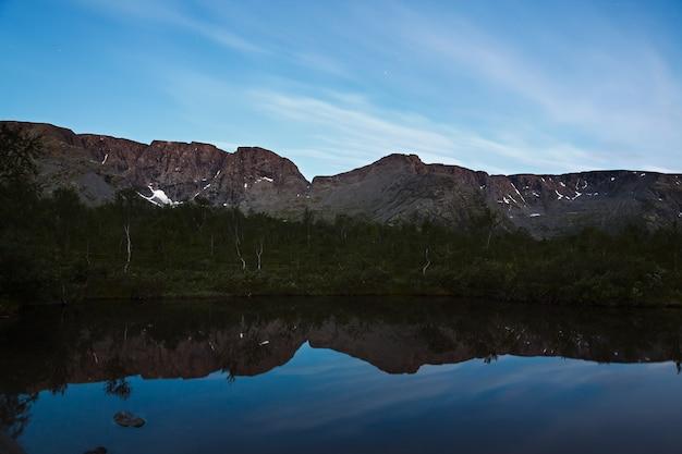 O céu com as estrelas ao amanhecer, refletido na água de um lago de montanha.