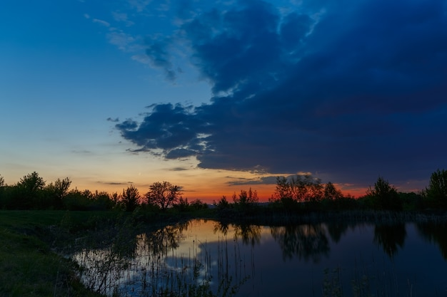 O céu com nuvens brilhantes iluminadas pelo sol após o pôr do sol sobre o lago.