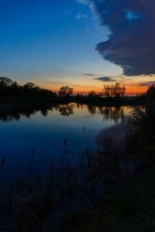 O céu com nuvens brilhantes iluminadas pelo sol após o pôr do sol sobre o lago