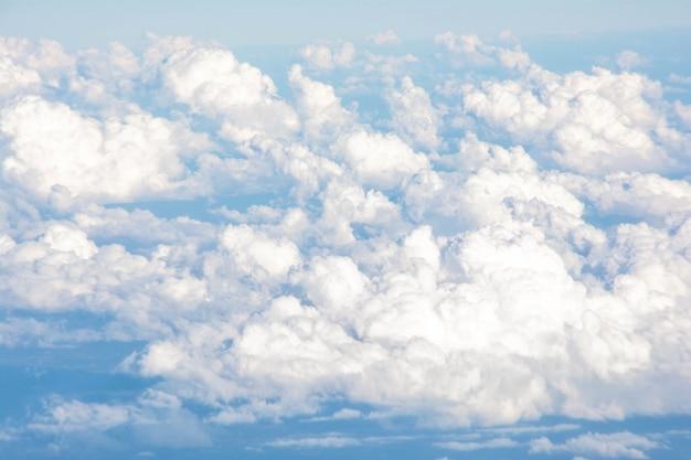 O céu e as nuvens brancas no dia brilhante ajardinam o fundo.
