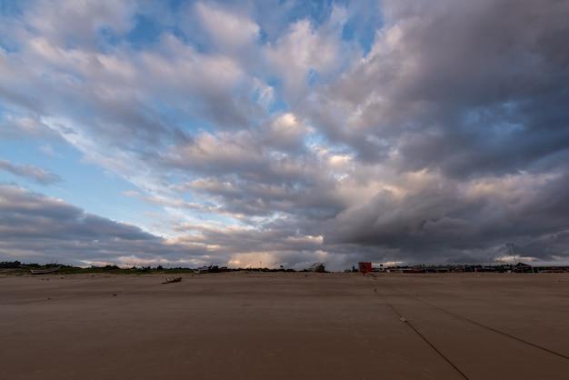 O céu está coberto de nuvens escuras e a praia está nublada