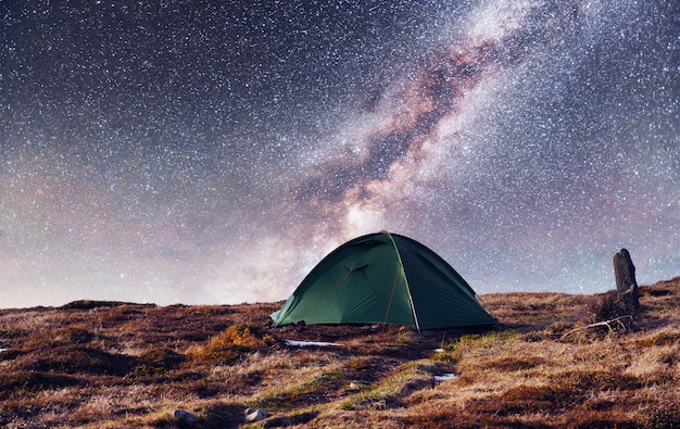 O céu estrelado acima da tenda nas montanhas.