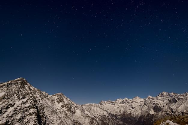 O céu estrelado acima dos alpes no inverno sob o luar