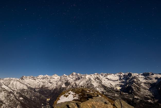 O céu estrelado acima dos alpes no inverno