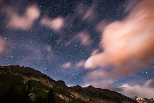 O céu estrelado com nuvens de movimento borrado e luar brilhante. alpes europeus