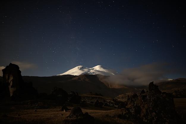 O céu estrelado da noite sobre elbrus. a montanha é iluminada pela luz da lua cheia. cáucaso do norte.