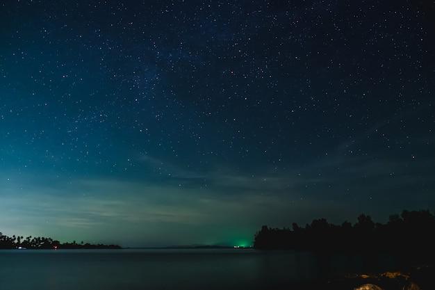 O céu estrelado e a paisagem marinha à noite