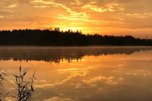 O céu laranja ao pôr do sol sobre o lago reflete na superfície da água parada, a silhueta da linha da floresta escura no horizonte