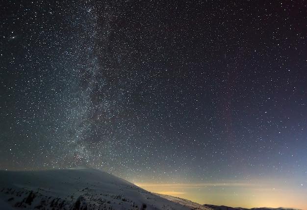 O céu mágico estrelado com névoa rosa está localizado acima da estação de esqui de inverno. o conceito de férias no campo e desfrute da natureza intocada.