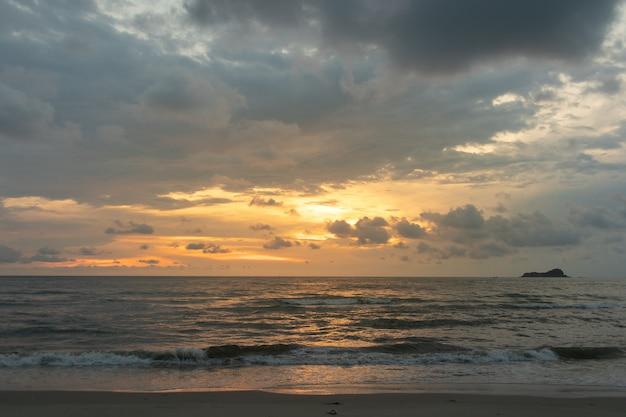 O céu nebuloso do por do sol dourado em calmo e limpa a praia.