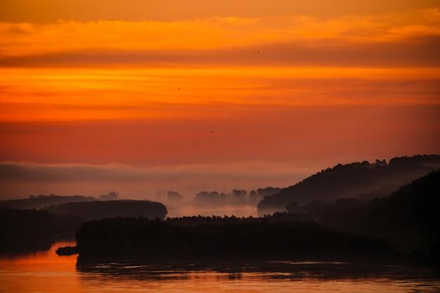O céu vermelho do amanhecer refletiu na água no vale do rio. neblina da manhã na distância acima da floresta na costa. pássaros voando no céu ao nascer do sol. nevoeiro na margem do rio.