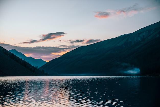 O céu vívido do amanhecer se reflete no puro lago alpino perto das silhuetas das montanhas ao nascer do sol
