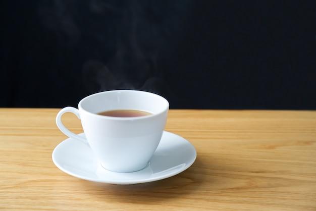O chá amarelo em um copo branco pôs sobre um saucer branco com vapor quente sobre o copo.