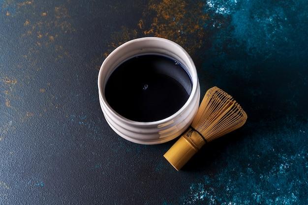 O chá azul do matcha em uma bacia e o bambu chasen no fundo azul, vista superior.