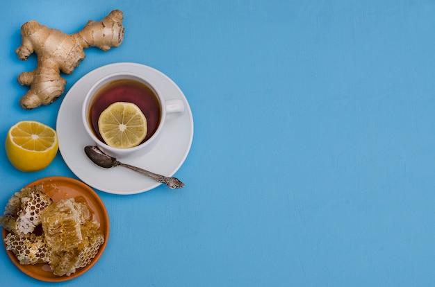 O chá com limão, mel e gengibre enraíza em um fundo azul com espaço da cópia, vista superior. prevenção de resfriados, para aumentar a imunidade no outono e inverno.