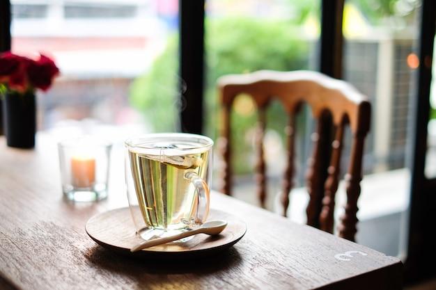 O chá de lavanda quente em vidro servir com colher de pau e pires