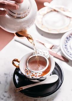 O chá de maçã quente serviu derramando da caneca através do infuser do filtro do chá do aço inoxidável no copo.