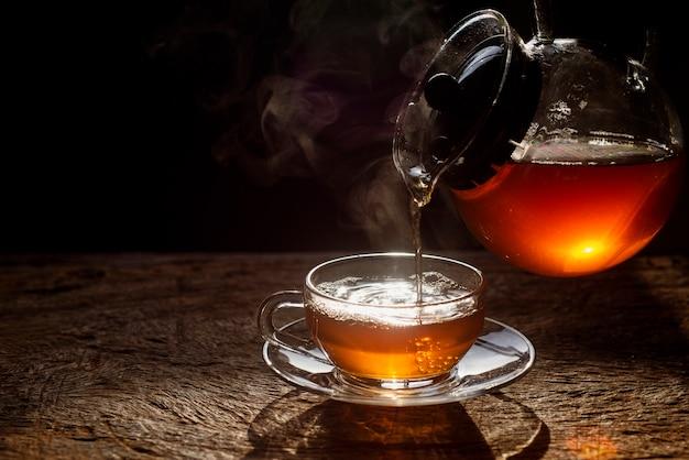 O chá está sendo derramado do bule colorido brilhante