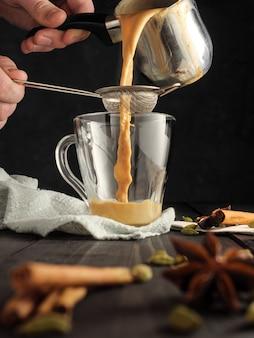 O chá masala é derramado por uma peneira em uma caneca de vidro. as espécies estão na mesa.