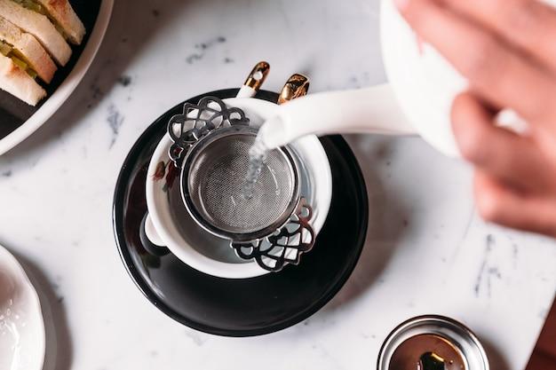 O chá quente do mirtilo da ervilha de borboleta serviu derramando da caneca com o infuser de aço inoxidável do chá.