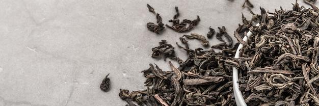O chá secado é derramado em um copo cerâmico branco em um cinza texturizado.