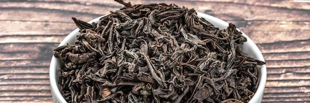 O chá seco é servido em uma xícara de cerâmica sobre uma mesa de prancha de madeira.