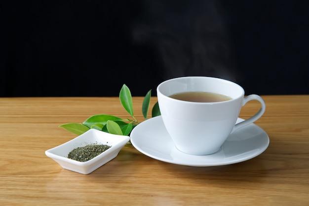O chá verde em um copo branco pôs sobre um saucer branco com vapor quente sobre o copo.