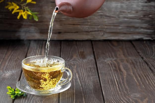 O chá verde quente é derramado do bule na tigela de vidro