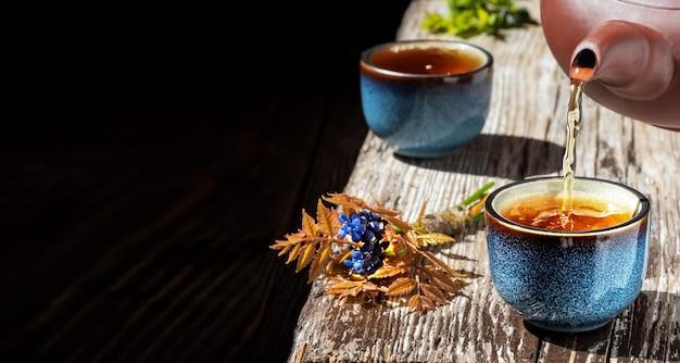 O chá verde quente é despejado do bule na tigela azul