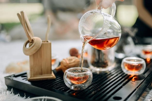 O chá vermelho em um bule de vidro é servido em xícaras. cerimônia do chá no parque pela manhã