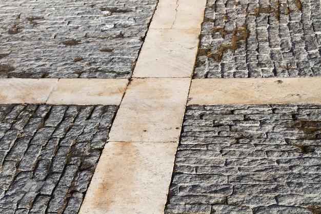 O chão de uma rua com paralelepípedos e mármore no centro da cidade
