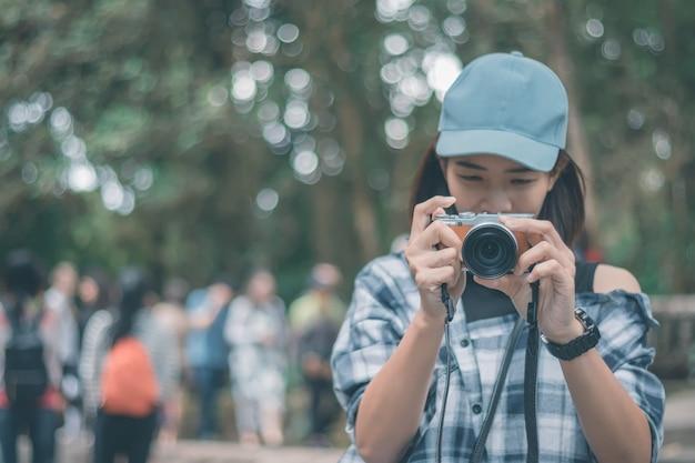 O chapéu do desgaste de mulher nova relaxa fora na floresta e toma uma foto.