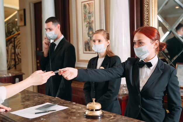 O check-in do hotel. recepcionista no balcão do hotel usando máscaras médicas como precaução contra vírus. mulher jovem em viagem de negócios fazendo check-in no hotel