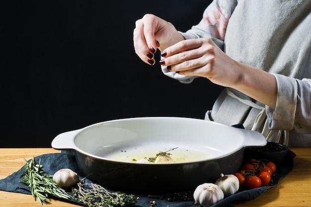 O chef adiciona alecrim à assadeira. o conceito de cozinhar batatas assadas.