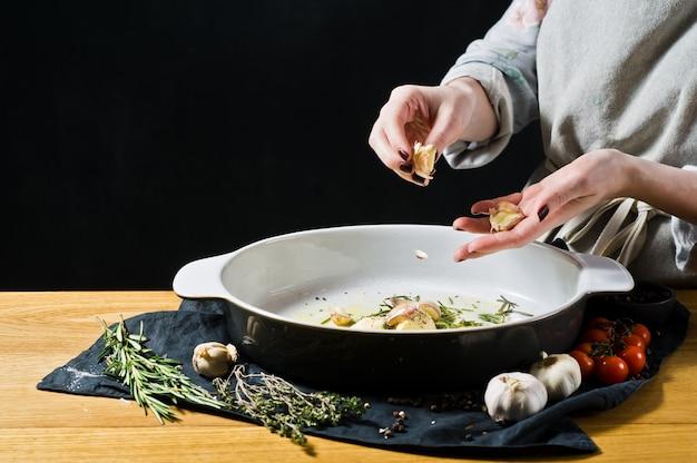 O chef adiciona alho à assadeira. o conceito de cozinhar batatas assadas.