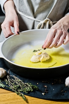O chef adiciona tomilho à assadeira. o conceito de cozinhar batatas assadas.