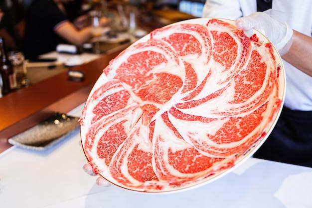 O chef apresenta a carne rare slices kagoshima wagyu com uma textura altamente marmorizada.