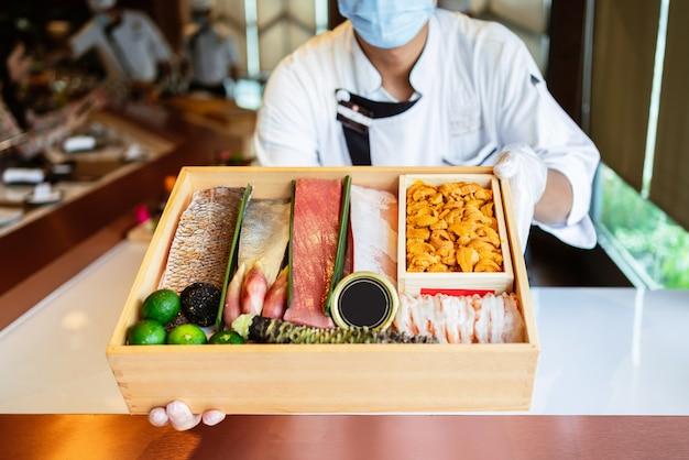O chef apresenta os ingredientes frescos em uma caixa de madeira antes de preparar a refeição omakase.