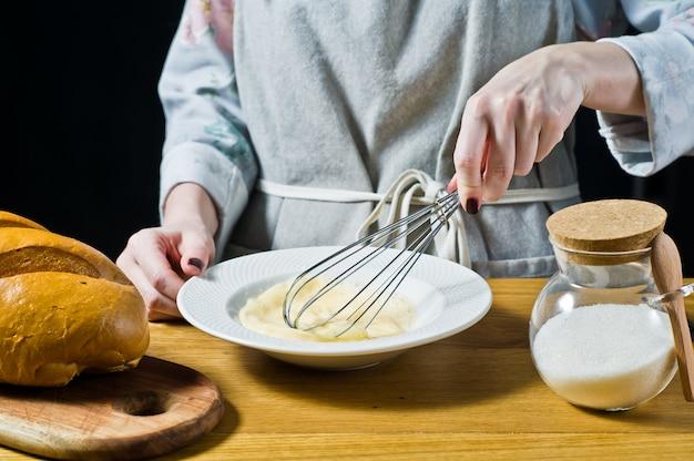 O chef chicoteia ovos com leite e açúcar em um prato. o conceito de cozinhar torradas.