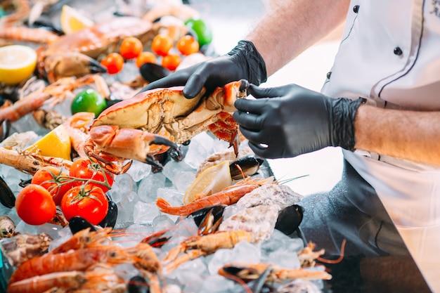 O chef coloca os frutos do mar em uma bandeja no restaurante.