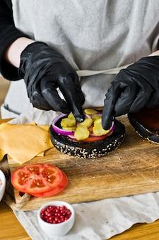 O chef coloca pickles em um cheeseburger. o conceito de cozinhar um hambúrguer preto. receita de hambúrguer caseiro.