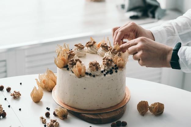 O chef confeiteiro decora o bolo com bolo caseiro de nozes e frutas, fazendo doces caseiros em uma cozinha branca Foto Premium