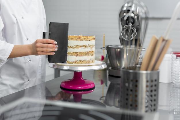 O chef confeiteiro nivela o bolo com creme