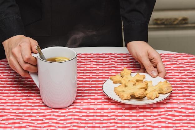 O chef cook serve biscoitos e uma bebida quente.